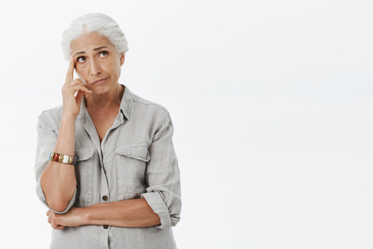 Portrait of troubled and concerned gloomy senior woman with white hair smirking holding finger on temple and looking at upper right corner thinking trying create plan in mind over grey wall