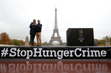French pastry chief Christophe Michalak and ACF Chairman Thomas Ribemont, pose in front of the Eiffel Tower during the launching of international campaign StopHungerCrime by French non-government organization (NGO) Action Contre la Faim in Paris