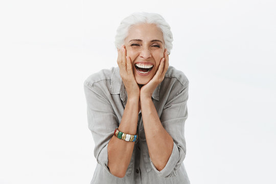 Life only starts when get older. Portrait of charming happy and carefree european senior woman with grey hair laughing out loud from jou and amusement holding palms on cheeks bending from laughter