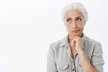 Displeased thoughtful and wise senior woman with gray hair smirking from dislike and irritationg thinking looking at upper left corner holding hand on chin posing against white background