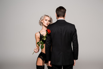 Seductive woman in lingeriewith red rose near man in black costume isolated on grey
