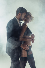Man hugging blonde wonderful woman in lingerie while she pulling him by cravat on grey smoke background