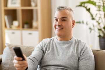 people, television and entertainment concept - man with remote control watching tv at home