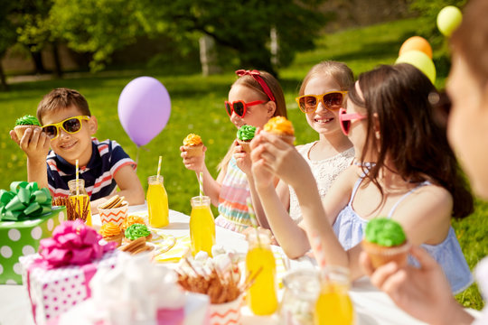 holidays, childhood and celebration concept - happy kids in sunglasses sitting at table on birthday party at summer garden and eating cupcakes