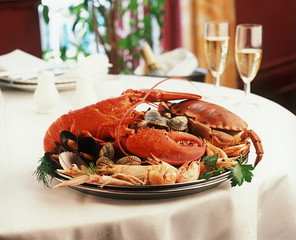 Seafood platter, lobster, shrimp, crab, restaurant setting.