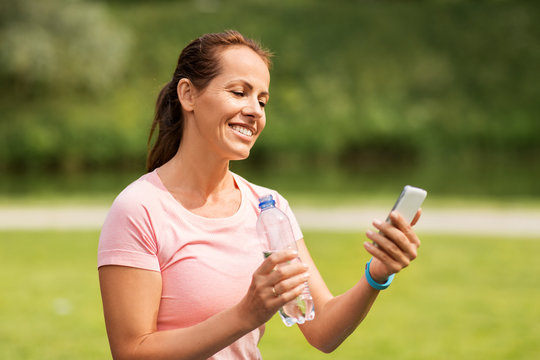sport, technology and healthy lifestyle concept - woman with smartphone and fitness tracker drinking water after exercising in park