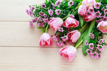 Pink tulips and chrysanthemums on wooden background