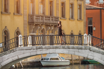 Travel to Italy. Girl standing on the bridge in Venice. Beautiful well-dressed woman posing on a bridge over the canal in Venice, Italy. Europe travel vacation. Woman traveling to Venice.