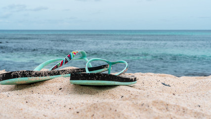 Colorful flip flops on a white sand beach with turquoise water. Summer vacation concept.
