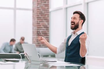 happy businessman sitting at the office Desk
