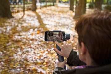 Senior woman records video with her smartphone placed on a gimbal in a park in autumn