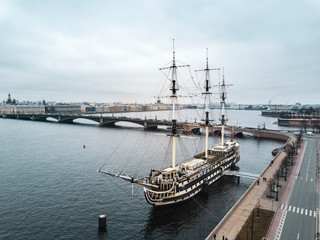 Aerial; drone view of cityscape, ship restaurant on the reconstructed linear three-deck frigate of the XVIII century; Troitsky bridge over the Neva river and Petropavlovskaya fortress background