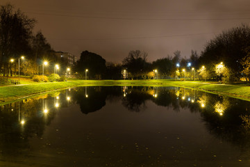 City pond with illumination around the radius with the reflection of lights