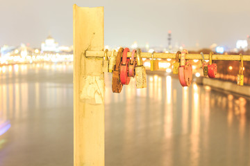 Barn locks are hung on the bridge in honor of love against the background of the river and the lights of the city