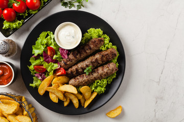 Traditional cevapcici served with baked potatoes. Flat lay. Stone background.