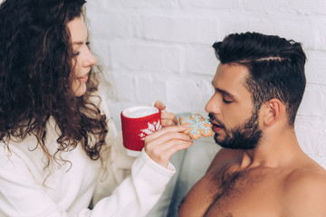 side view of beautiful woman with coffee cup feeding boyfriend by cookie in bedroom at home