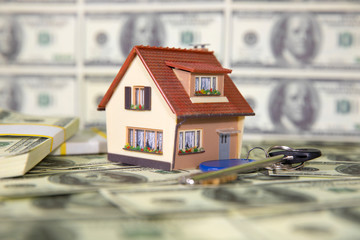 A small house with keys on the background of hundred dollar bills. Reduced copy of the house on the background of money. The keys to the purchased house.