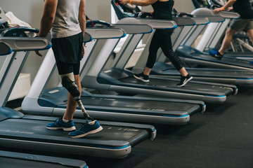 cropped shot of man with artificial leg running on treadmills at gym with other people