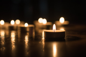 Small glowing candle on the floor on background of group of candles. Horizontal view