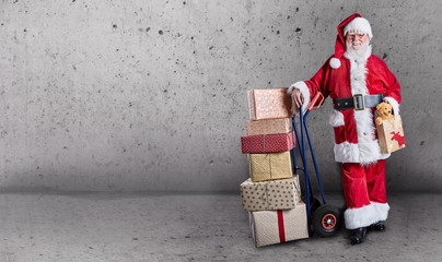 Santa Claus with gifts on trolley with copy space
