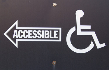 Handicapped Accessible Sign. Black sign with white writing and arrow pointing handicapped accessible entrance.