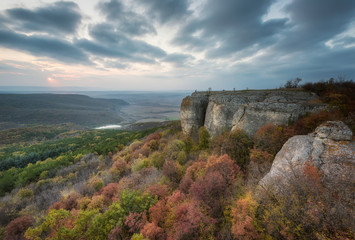 Autumn sunset. Amazing sunset view with rocks and autumn forest.