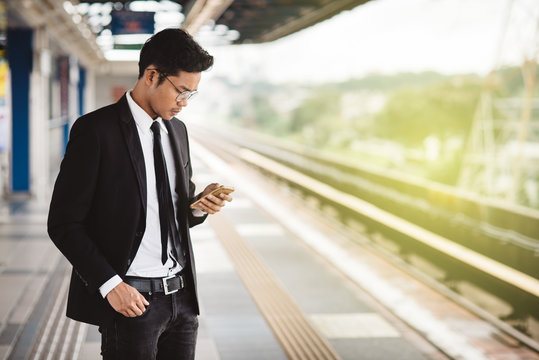 young asian hipster businessman with smartphone waiting at the train platform. Concept of wireless technology, public transport and business travel