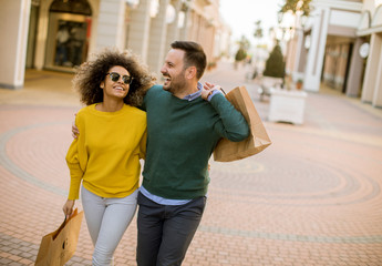 Young multiethnic couple with bags in the shopping