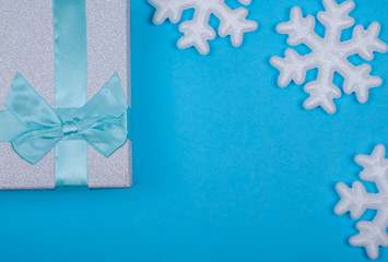 gift box with ribbon and snowflakes on blue background. new year background