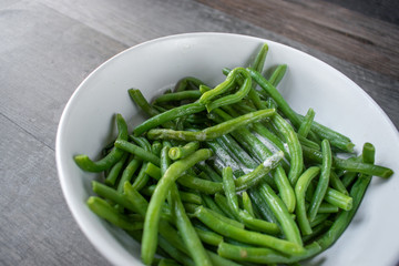 whole green beans with butter in white bowl