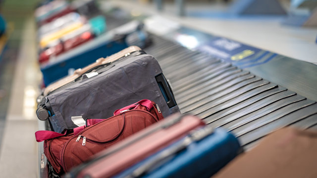 Passengers' Luggage Suitcase Travelling Bags On Conveyor Belt In Airport