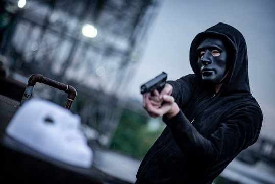 Mystery hoodie man in broken black mask pointing gun at white mask. Crime and violence concepts