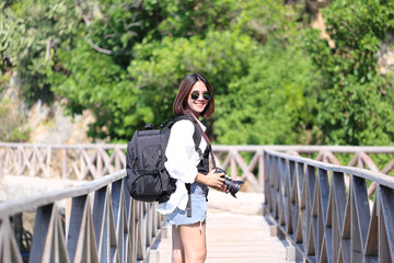 Young woman traveler with backpack enjoying and holding camera in his hands and standing on the bridge of the mountains background