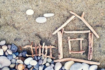 Image of a little house from wooden sticks on the sea pebble beach. Sea tour. Concept image house. Concept of sale or purchase house