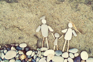 Symbolical images of family, figures of the man, woman and child  from sea pebbles on the seashore. Conceptual image of a strong and close-knit family