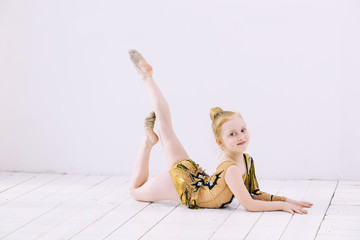 Little Child Girl gymnast doing stretching in a bright room on a happy and cute
