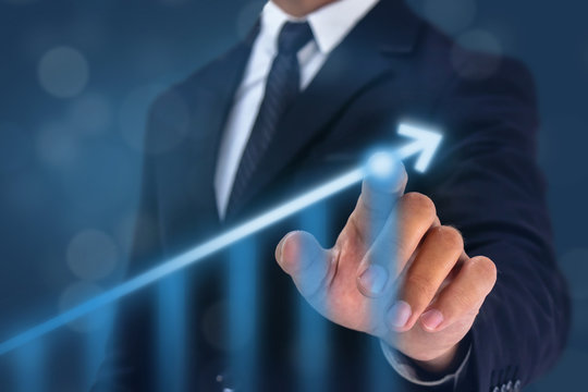 business man point hand on the top of arrow graph with high rate of growth. The success and growing growth graph in the company or industrial after investment