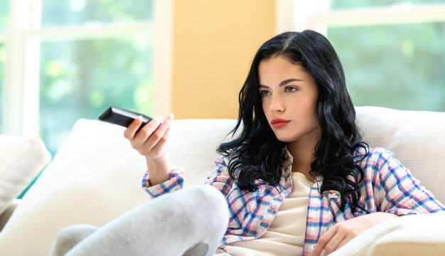 Young woman holding a TV remote control in a bright interior room