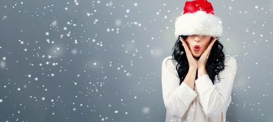 Woman with a Santa hat pulled over her eyes on a gray background