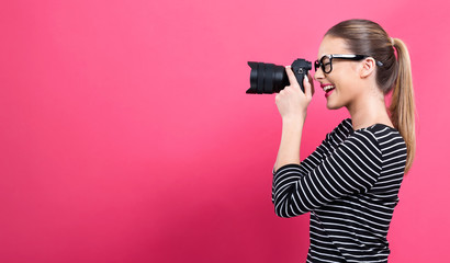 Young woman with a professional digital SLR camera on a pink background