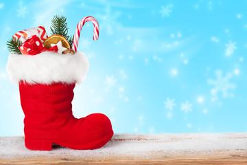 Weihnachtsmann Stiefel gefüllt mit Süßigkeiten und Geschenken mit Schnee Hintergrund
