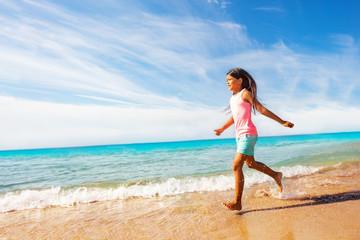 Sporty Asian girl running along sandy beach