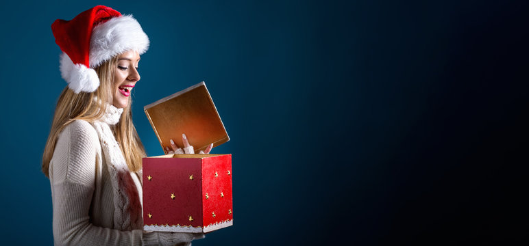 Young woman with santa hat opening a Christmas gift box on a dark blue background