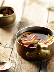 mulled wine with cinnamon and orange on a wooden background