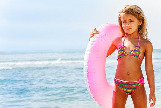 Beautiful girl posing with swim ring on the beach