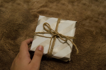 woman hand holding a gift box against brown background