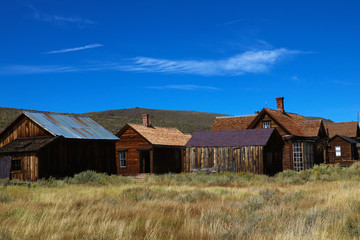 Colored vintage old looking photo of empty streets of abandoned ghost town Bodie in California, USA