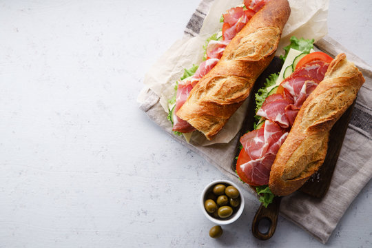 Top view of two fresh baguette sandwiches bahn-mi styled with olives. Ham, sliced cheese, tomatoes and fresh lettuce on dark wooden cutting board on concrete background. Top view, text space