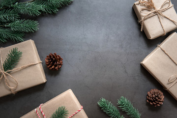 Christmas background with decorations and gift boxes on black floor.