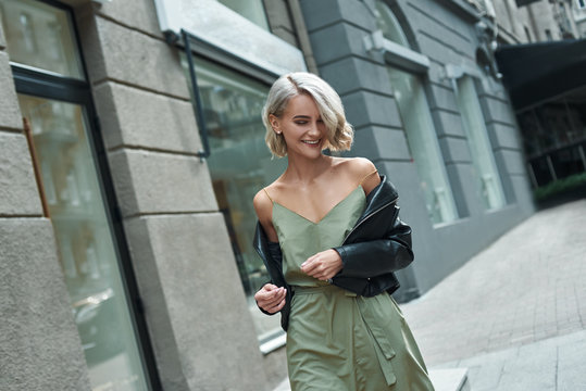 Fashion. Young stylish woman walking on the city street looking down laughing playful